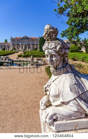 Queluz, Portugal. Sphinx sculpture at the Neptune gardens and Cerimonial Facade on the Queluz Royal Palace. Formerly used as the Summer residence by the Portuguese royal family.