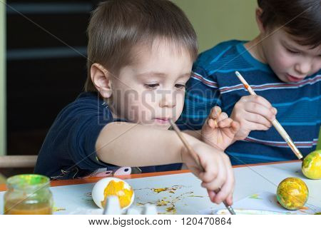 Two boys painting the eggs for Easter