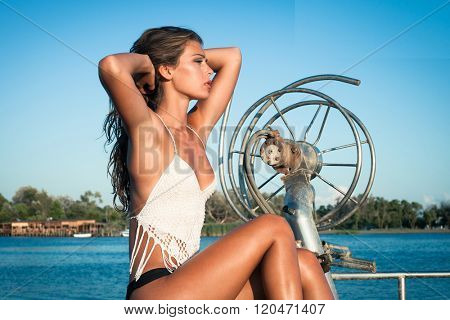 tanned young woman enjoy in  summer sun at sea on old fishing boat side view