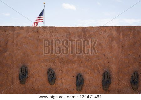 FAYETTEVILLE, NC - JUNE 28, 2015: Bronze casted hands from North Carolina veterans on the Oath of Service Wall aka, The Soils Wall, made of native soil from the state, American Flag in background.