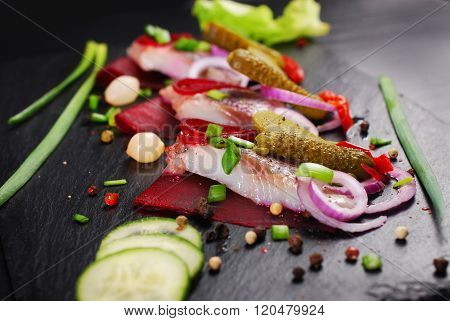 Herring Appetizer With Beets And Gherkin On Black Slate Board