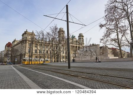 BUDAPEST, HUNGARY - FEBRUARY 02: Pedestrians walking on pavement next to tram line near Hungarian Parliament building, with Museum of Ethnography in the background. February 02, 2016 in Budapest.