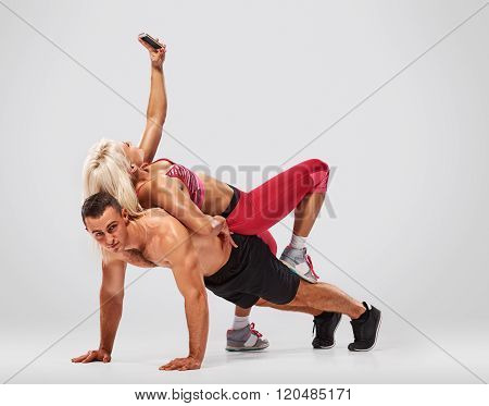 man doing push ups but woman selfie