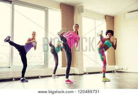 fitness, sport, training, gym and martial arts concept - group of women working out fighting technique in gym