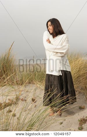 Full view portrait of woman standing in sand at beach
