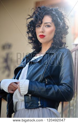 Charming young curly brunette woman with black leather jacket. Sexy gorgeous young woman