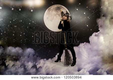 A witch in black clothes with a broom