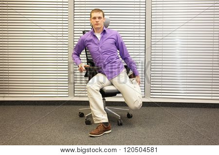caucasian man exercising on chair in office, healthy lifestyle
