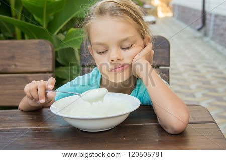 Upset Six Year Old Girl Looking Sadly At The Semolina In A Spoon At Breakfast