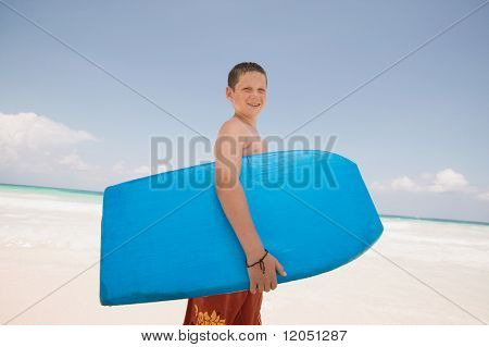 Young boy holding a boogie board at the beach