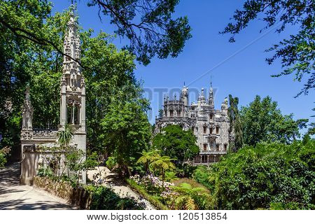 Sintra, Portugal - July 14, 2015: Close up of the Chapel with the Regaleira Palace and Gardens in background. A neo-manueline palace decorated with alchemy and freemasons symbols.