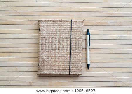 A workbook with sedge cover and a pen.