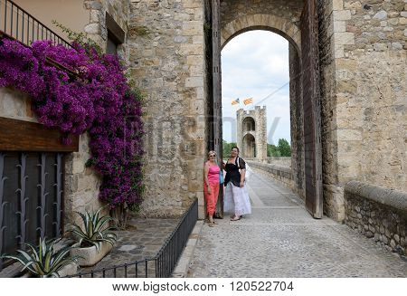 Tourist Women Near Gate Of Old Bridge In Besalu, Spain.