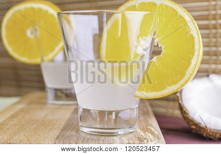 Fresh Coconut Water In Glass Decorated With Orange Slices On Wooden Tray And Bamboo Background Selec