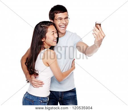 Young Interracial couple, hispanic man and asian girl, having fun laughing out loud and taking selfie on smartphone isolated on white background - humor or communication concept