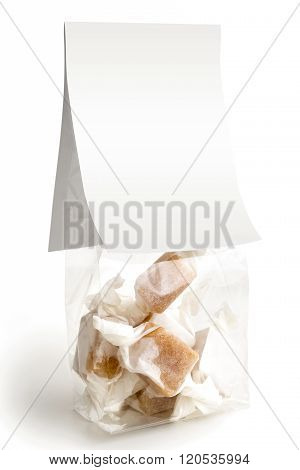 Isolated Cellophane Packet Of Wrapped Caramel Toffees. Empty Label.