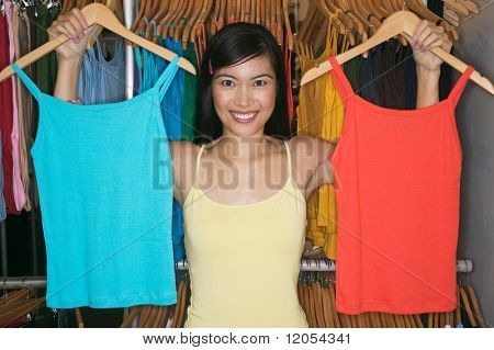 Young woman comparing blue and red tank tops