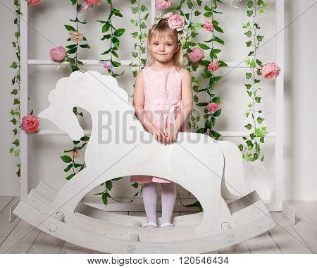 Portrait Of A Little Blonde Girl  Standing Near The Wooden Horse Rocker