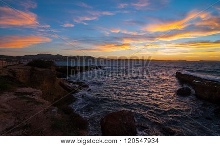 Golden sunset behind Conejera Islands.  Balearic sea churns waves on rocks.  Evening in Ibiza.