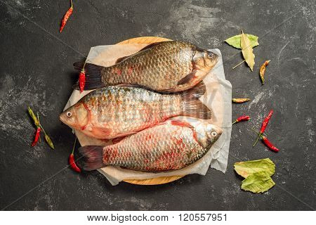 Three Raw Carp Fishes On A Plank Board Over Old Black Background