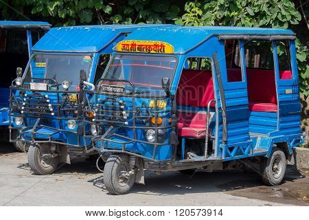 RISHIKESH INDIA - OCTOBER 20 2014 : Auto rickshaw taxis on a road. These iconic taxis have recently been fitted with CNG powered engines in an effort to reduce pollution