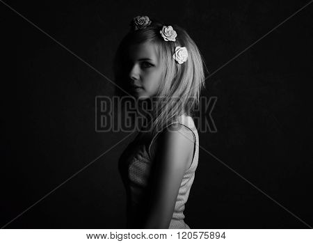 Black and white emotional portrait of young girl in the dark