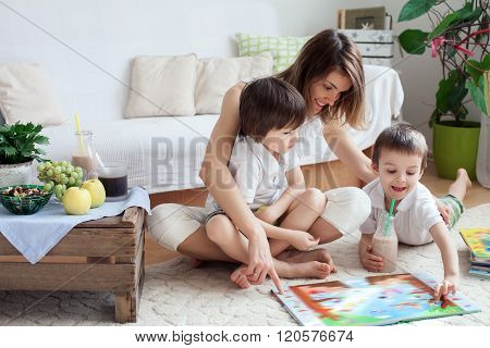 Young Mother, Read A Book To Her Tho Children, Boys, In The Living Room