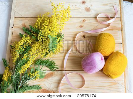 A Sprig Of Mimosa With A Pink Ribbon And Yarn Coil On A Wooden Background