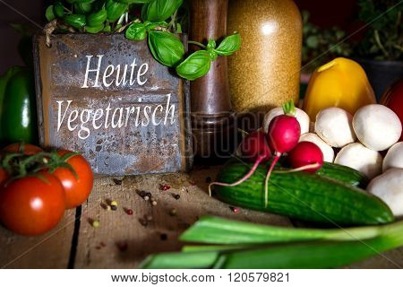 A Lots Of Healthy Vegetables On A Wooden Table, Sign With Text Heute Vegetarisch