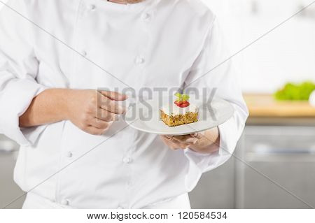 Chef holding dessert cake with strawberry