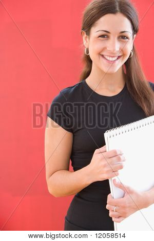 Portrait of woman with notebook in hand