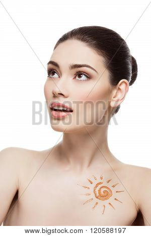 Girl with cream sun shape drawing on chest