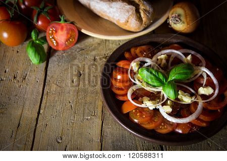 Tomato And Onion Salad With Rustic Bread On A Old Wooden Table