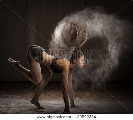 Ballerina dancing with flour on dark background