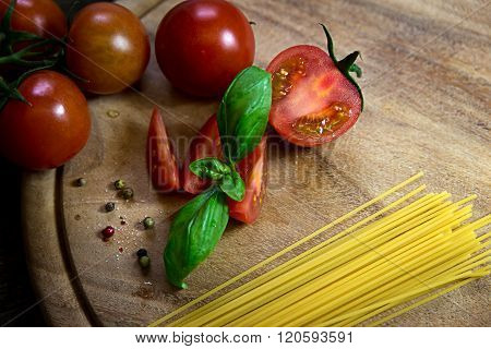 Tomatoes And Basil With Spaghetti And Pepper On A Wooden Plate