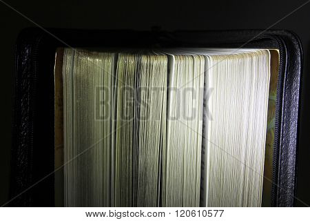 Semi Open Black Book With Golden Pages