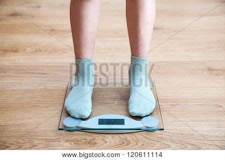 Girl's Legs Standing On The Scales