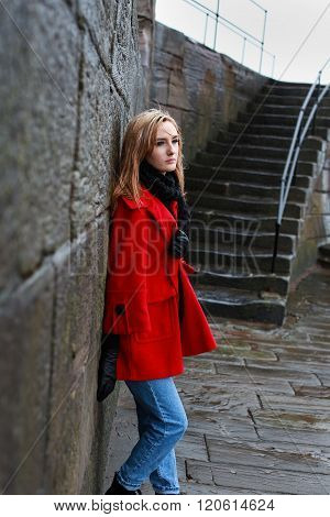 Woman In A Red Coat Leaning On An Old Stone Wall In The Sleet And Rain
