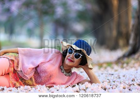 Woman With Fallen Pink Trumpet Flowers