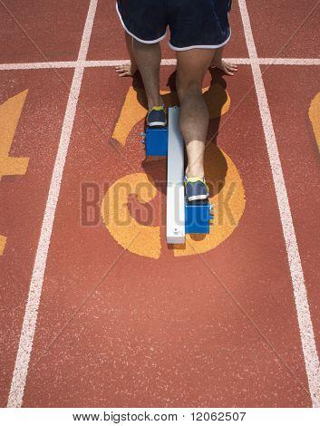 Vista posterior de atleta de pista en la línea de salida