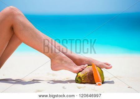 Female tanned smooth legs with suncream and coconut on white beach