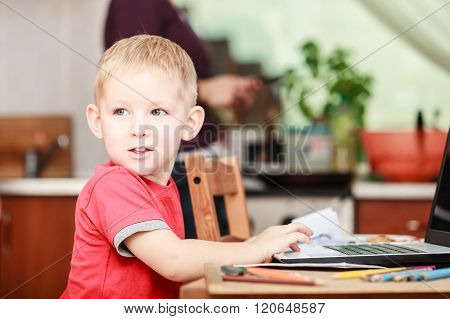 Little Boy With Laptop On Table In Home.