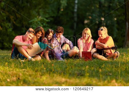 Group Of Happy Students With Book  In The Park