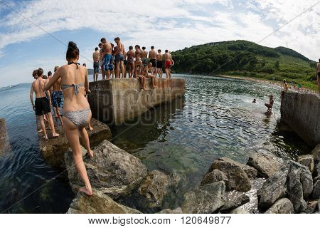 NAKHODKA, RUSSIA - JULY 29, 2015: Joyful boy and girl jumping into the sea from the old pier. Local children love to relax, sunbathe, swim and dive in the sea bay near the city of Nakhodka.