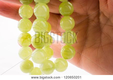 Hand holding a green beads on a white background