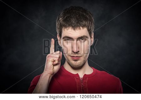 Young man shows finger up.