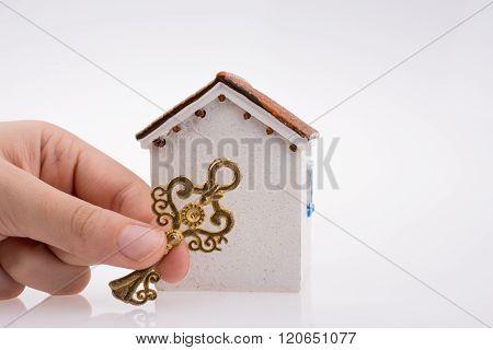 Hand Holding A Key Near A House