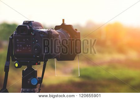 DSLR camera with gradient filter focus on sunrise landscape view.