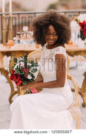 Wonderful black bride happily smiling with eyes closed and holding a bouquet of red flowers. Wedding