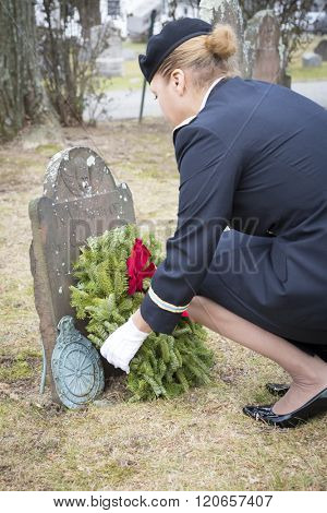 SUCCASUNNA, NJ-DEC 12, 2015: U.S. Army Lt. Col. Ingrid Parker, Garrison Commander at Picatinny Arsenal places a wreath on the grave of Private Joshua Case during the 2015 Wreaths Across America event.